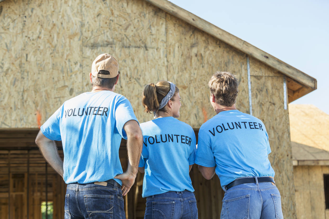 A group of three volunteers helping to build a house for a family in need. One woman stands in the middle between two men. Their backs are to the camera, showing the word VOLUNTEER written on the back of their blue shirts.