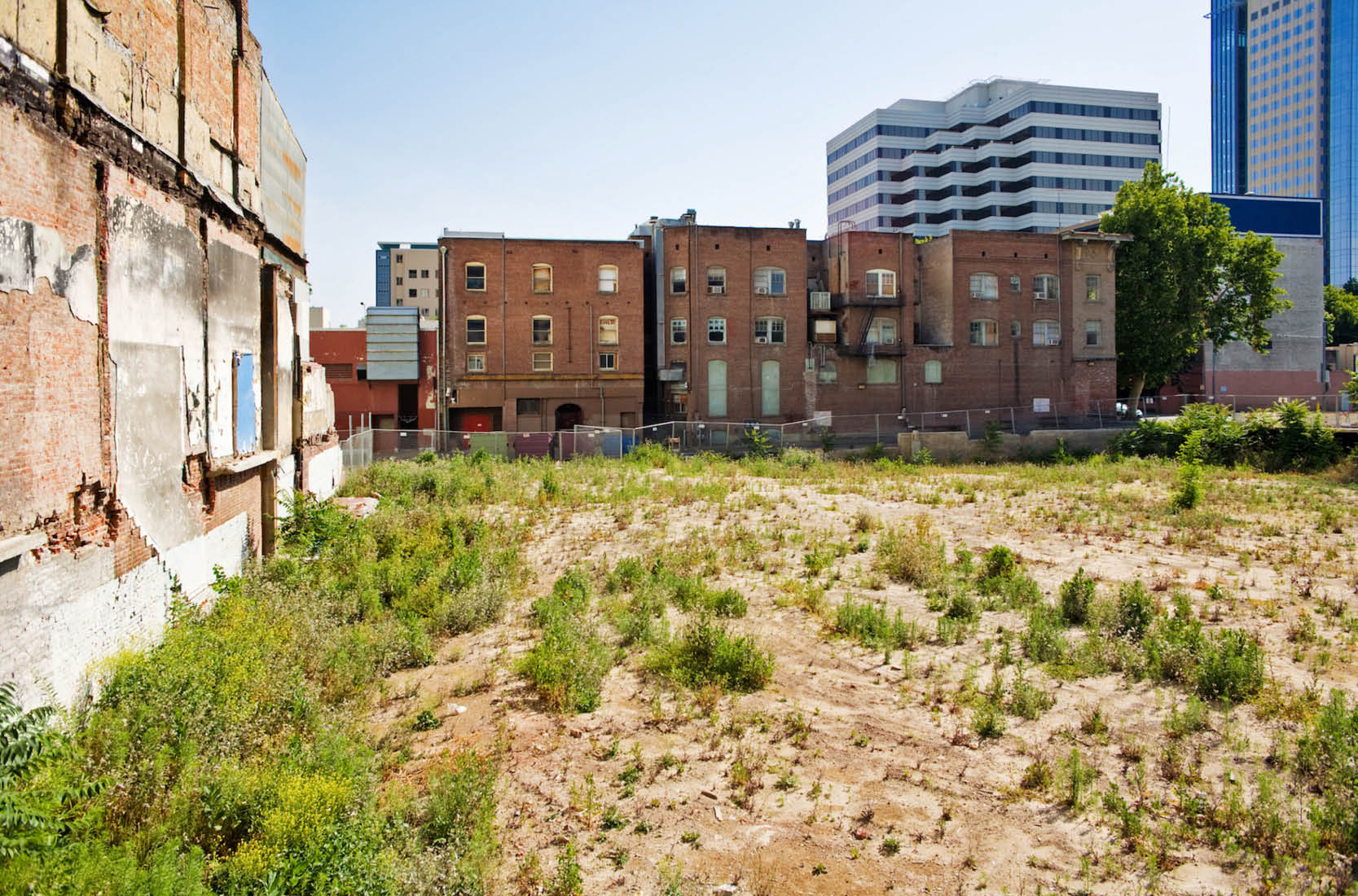Decaying buildings and patchy grass.