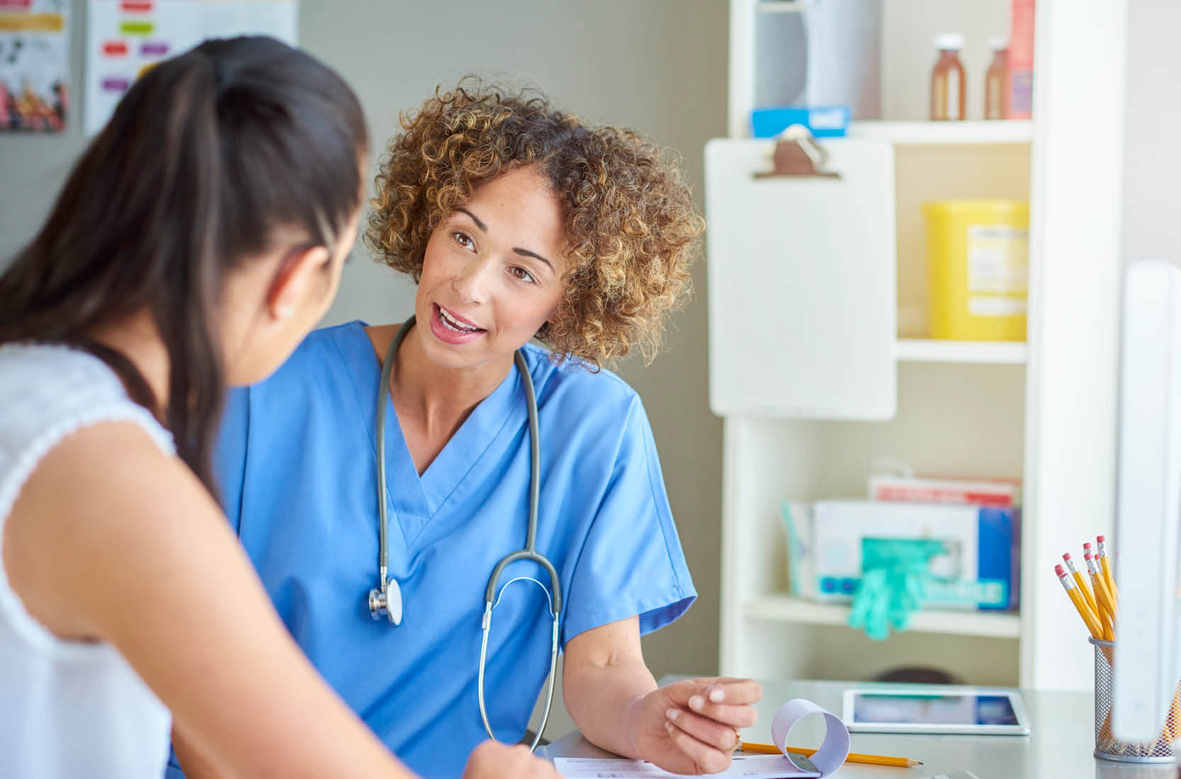 Woman doctor talking to woman patient.