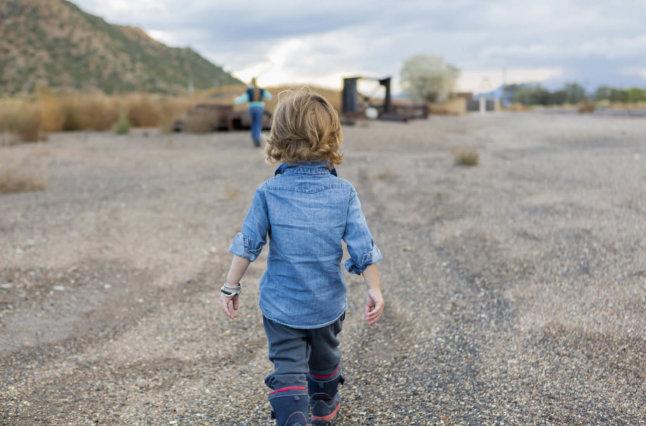 Child walks towards mother in desolate area.