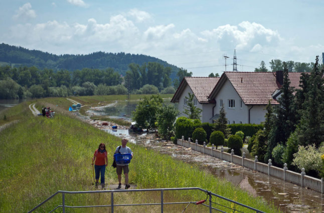 Two people walk along path in rural area.