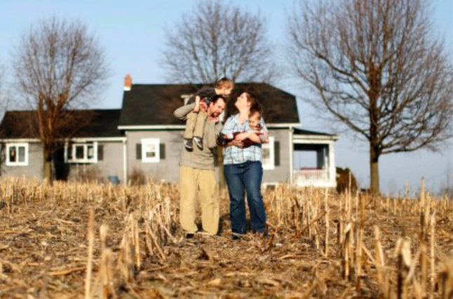 Young family standing in corn field in front of house.