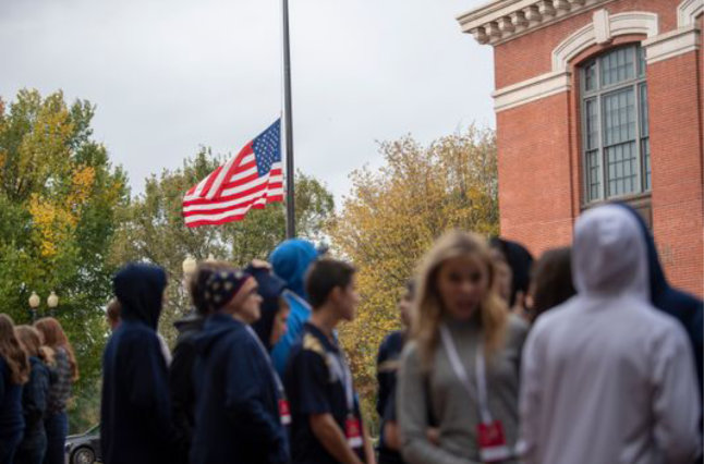Students walking with flag at half-staff