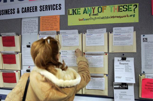 Woman looking at job postings on wall.