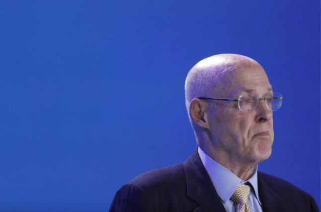 Hank Paulson stating in front of blue background.