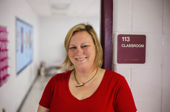 Teacher stands in front of classroom.
