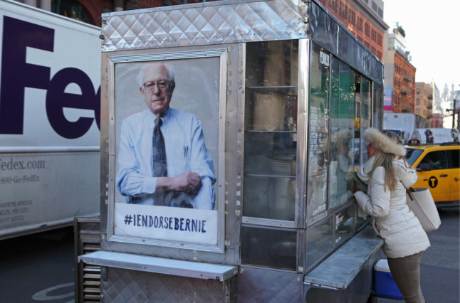 A New York coffee cart displays a photo endorsing US presidential candidate Bernie Sanders, Democrat Vermont. The cart is located on Lafayette Street south of Houston Street. An unknown woman is ordering coffee from the vendor. In the background traffic heads north up Lafayette.