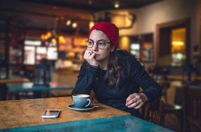 Young woman sitting alone in coffee house