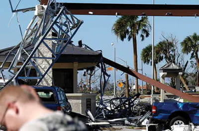 A soldier stands guard at the damaged entrance to Tyndall Air Force Base in Panama City, Florida, Oct. 11, 2018, after Hurricane Michael.