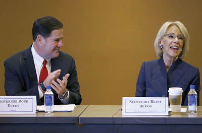 U.S. Education Secretary Betsy DeVos smiles as she is applauded by Arizona Gov. Doug Ducey during a roundtable discussion on school choice Dec. 5, 2019, in Scottsdale, Arizona. Ms. DeVos is a longtime school choice advocate.