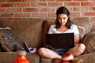 Young women sitting on a couch at home working on a laptop computer