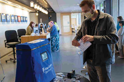 A masked Taylor Miller prepares to cast his ballot during early voting on Monday in Renton, Wash. King County has had the highest number of deaths in the U.S. linked to the coronavirus outbreak.