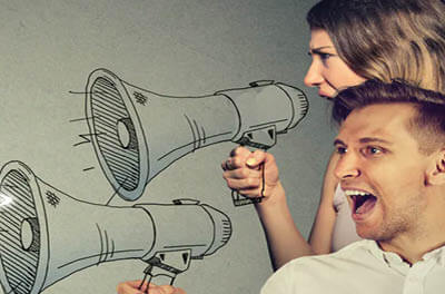 Man and woman yelling through megaphones