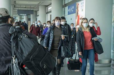 Travelers wearing protective masks walking through an airport terminal