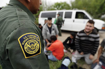 A Border Patrol agent speaks with a group of people suspected of entering the U.S. illegally near McAllen, Texas