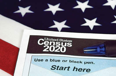 2020 Census questionnaire with pen sitting on U.S. flag
