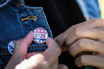 Young man pinning a 2020 vote button to his jacket