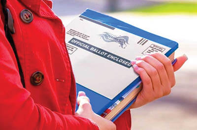 Woman carrying an vote-by-mail ballot from her mail