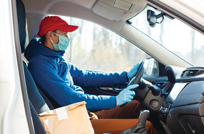 Gig economy worker wearing protective mask, driving van with takeout food order.