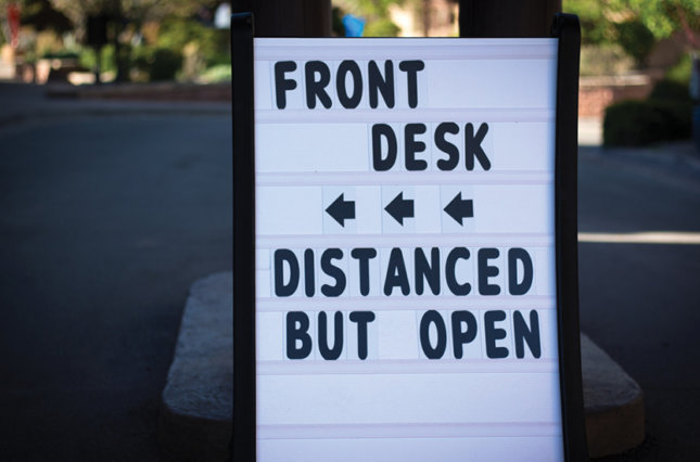 """Sign in front of hotel that reads """"front desk, distanced but open"""""""