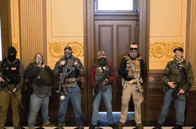 A militia group stands in front of the governor's office after protesters occupied the state capitol building during a vote to approve the extension of Gov. Gretchen Whitmer's stay-at-home order due to the coronavirus outbreak, in Lansing, Michigan, April 30, 2020.