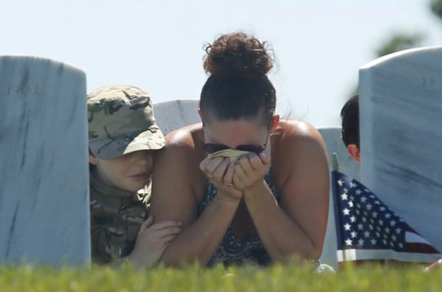 Widowed mother cries a the grave of her military husband