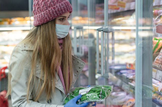 Young woman in supermarket wearing a protective mask