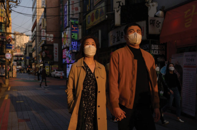 Couple wearing protective masks and walking hand in hand down a street in South Korea