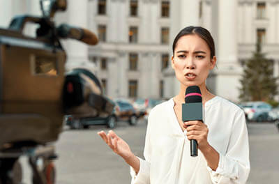 Female television news reporter on camera in front of an office building