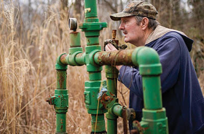 Hanson Rowe, a landowner who blames a leaky gas well on his property for health problems, smells for the odor of gas emanating from an abandoned well on his property in Salyersville, Kentucky