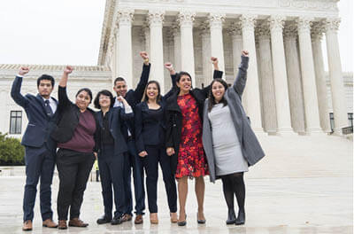 DACA recipients, including Carolina Fung Geng, (3rd from left), plaintiff Martin Batalla Vidal (center) and Eliana Fernández (3rd from right) hold their fists in the air as they enter the U.S. Supreme Court