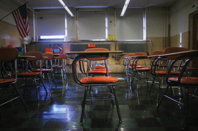 Rows of empty desks in a classroom