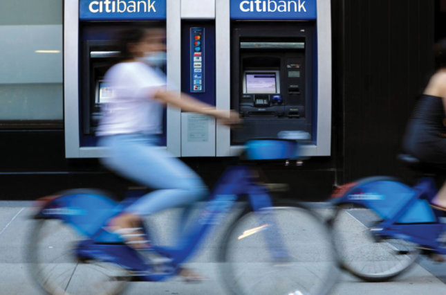 Cyclists wearing protective masks ride past a Citibank branch.