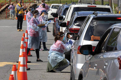 Healthcare workers administer COVID-19 tests to a long line of individuals in cars in Fairfax County, VA