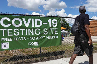 Photo of a man walking by a sign for a COVID-19 testing site