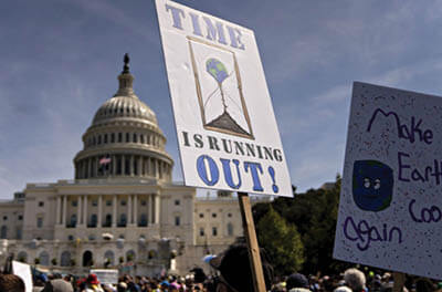 Signs held by climate change protesters in front of the U.S. Capitol building