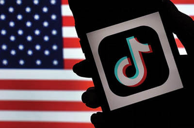 In this photo illustration, the logo for the social media app TikTok is displayed against the background of a U.S. flag on the screen of an iPhone.