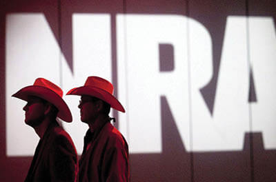 National Rifle Association members listen to speakers during its annual meeting in Houston in 2013. The NRA has been cutting staff and salaries amid the pandemic. The cuts come against the backdrop of internal turmoil, legal challenges, and a revolt among some of its members.