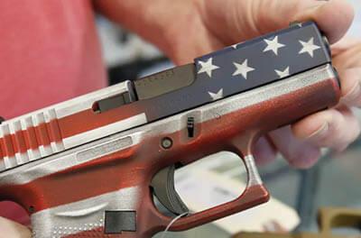 Man holding a handgun painted like an American flag