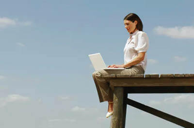 Woman sitting outside on a wooden dock using a laptop