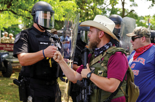 An armed far-right militia member fist-bumps a police officer in riot gear as various militia groups stage rallies at the Confederate memorial at Stone Mountain, Georgia, August 15, 2020