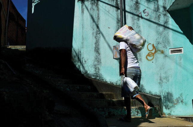 Man carries a bag of food through an impoverished borough