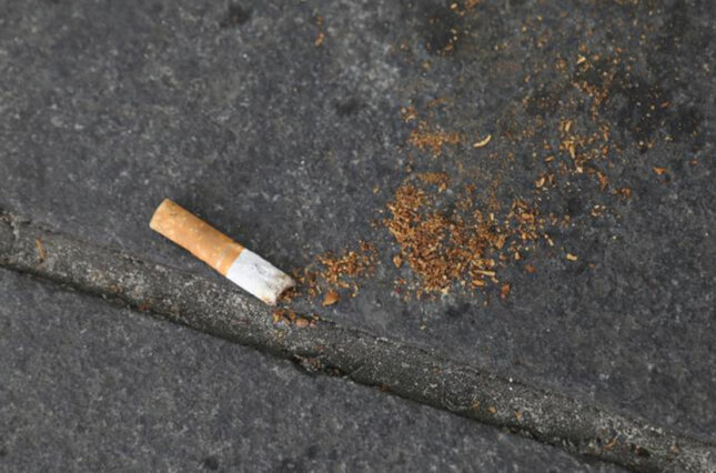 A cigarette butt lies on the street in New York City