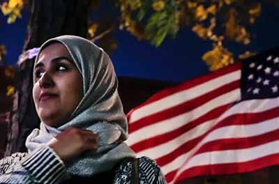 Muslim woman standing next to an American flag