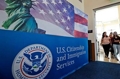 Three women immigrants entering a U.S. Citizenship and Immigration Services office